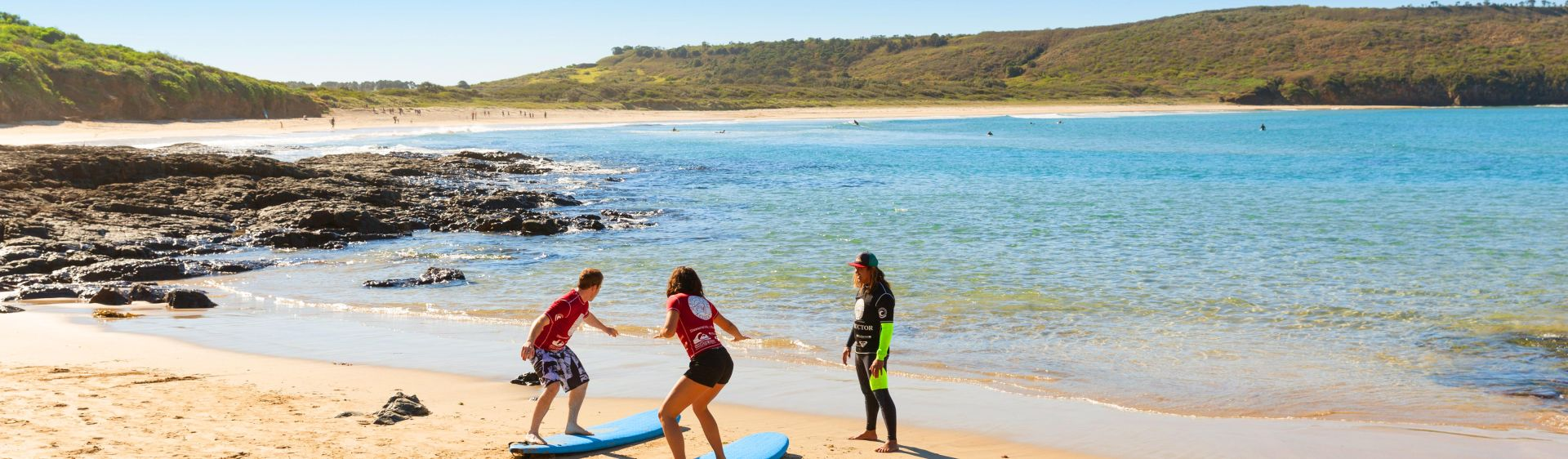 Couple taking a surfing lesson at The Farm, Killalea State Park, South Coast NSW