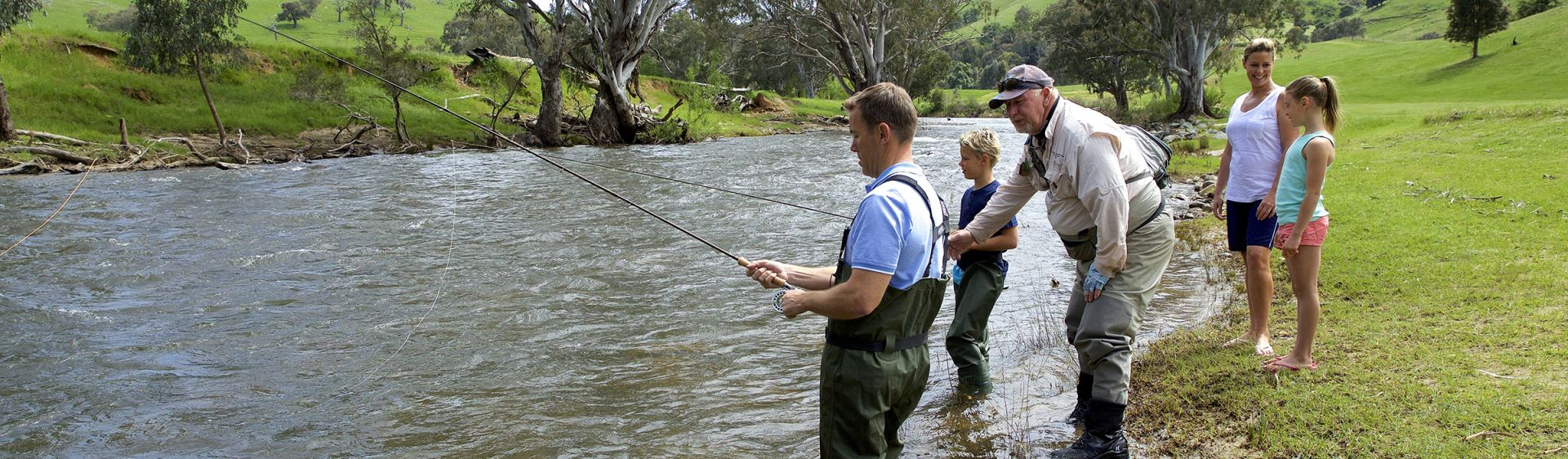Family enjoying a fly fishing lessons with guide Dave Ducker on the Goobarragandra River, Tumut