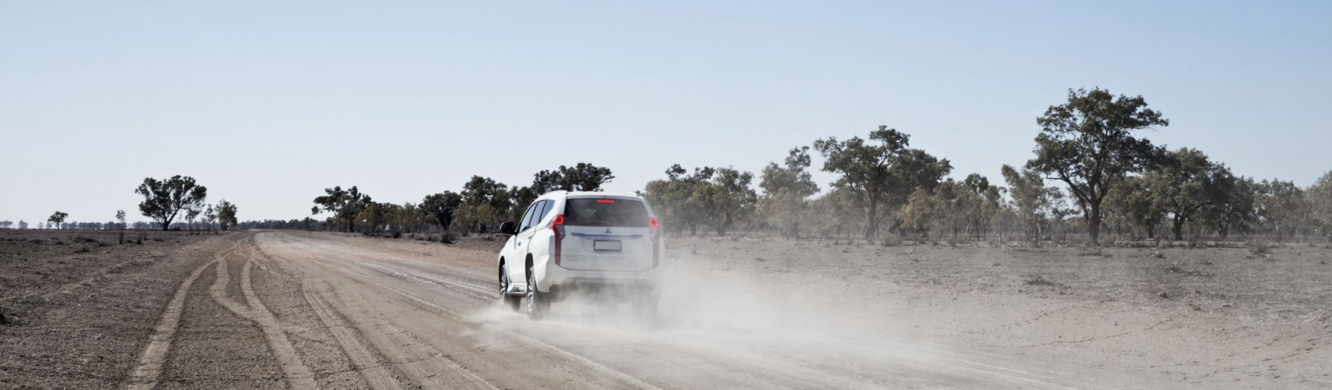A white four wheel drive drives along a dirt road in the Outback near Wilcannia