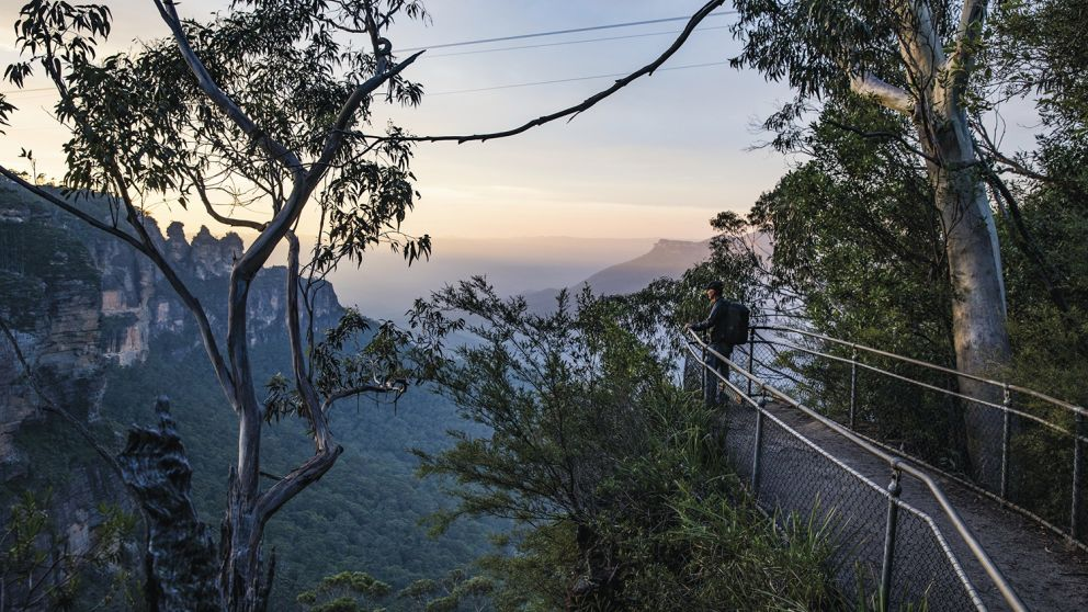 Man enjoying the sun rising over the Three Sisters from the Furber Steps-Scenic Railway walking track