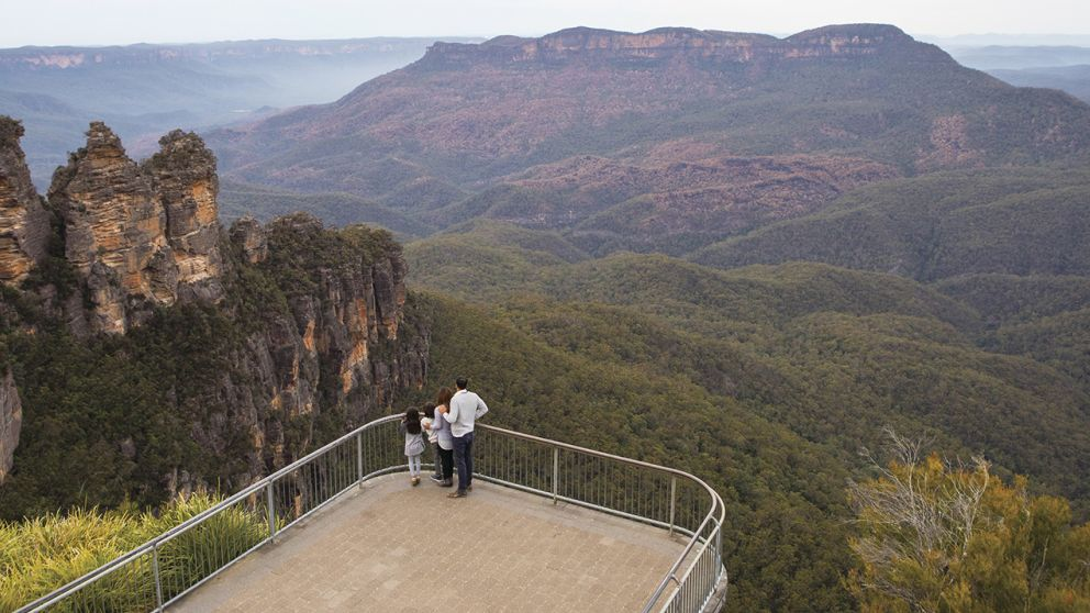 Family enjoying views across Blue Mountains National Park to the Three Sisters and Mount Solitary from Echo Point Lookout