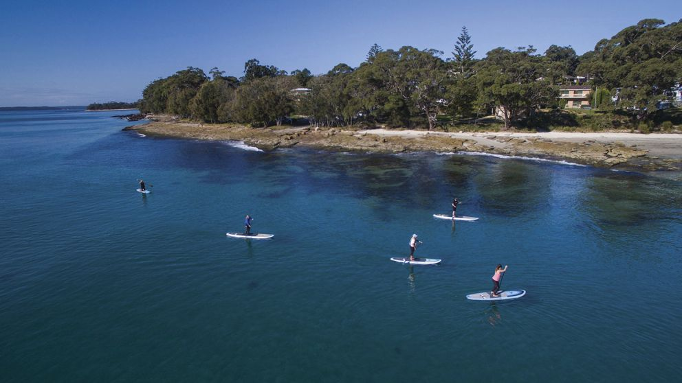 Group of friends enjoying a day on the water paddleboarding at Orion Beach, Vincentia