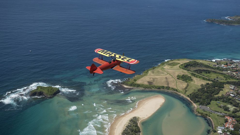 Southern BiPlanes Adventure aircraft soaring over the Shellharbour coastline on the South Coast