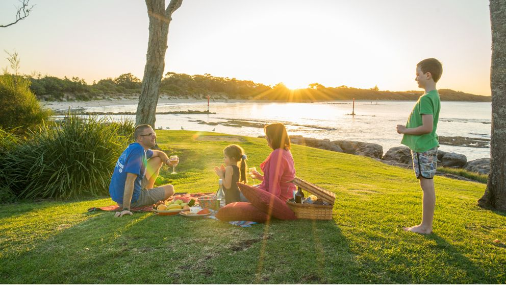 Family enjoying a picnic and a view of the sun setting over Currarong Beach on the South Coast