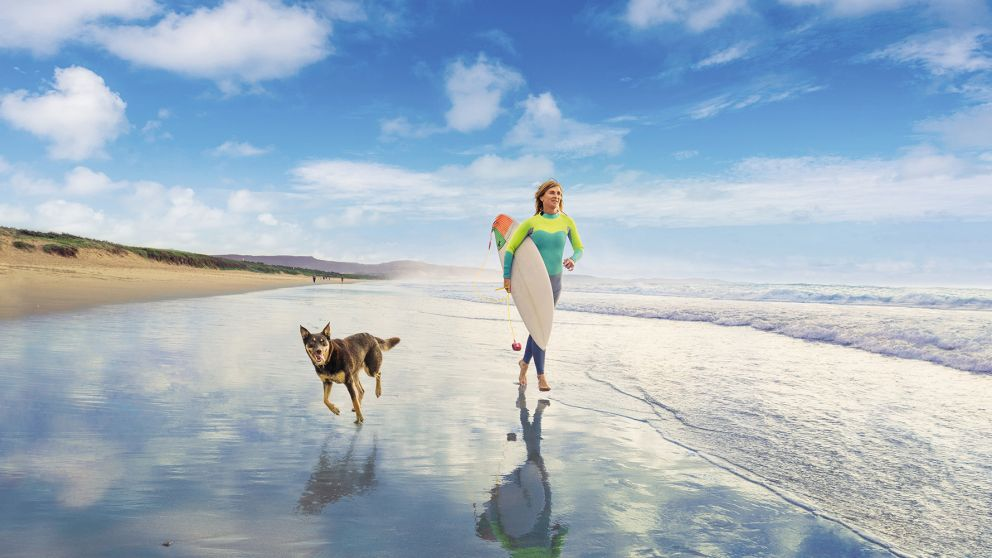 Woman and her pet dog out for a morning surf at Shoalhaven Heads on the South Coast
