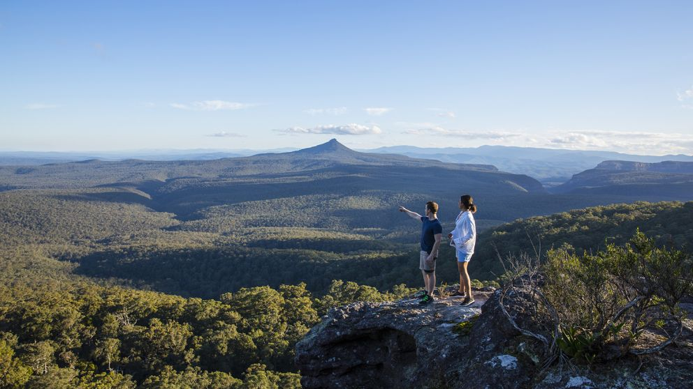 Couple enjoying panoramic views across to Pigeon House Mountain (Aboriginal: Didthul) in Moreton National Park