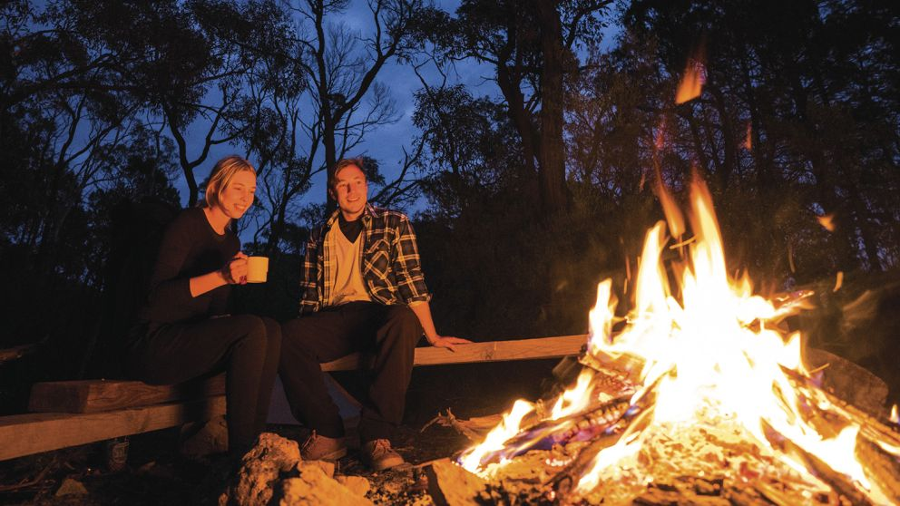 Couple by their campfire at Balor Hut Campground in Warrumbungle National Park