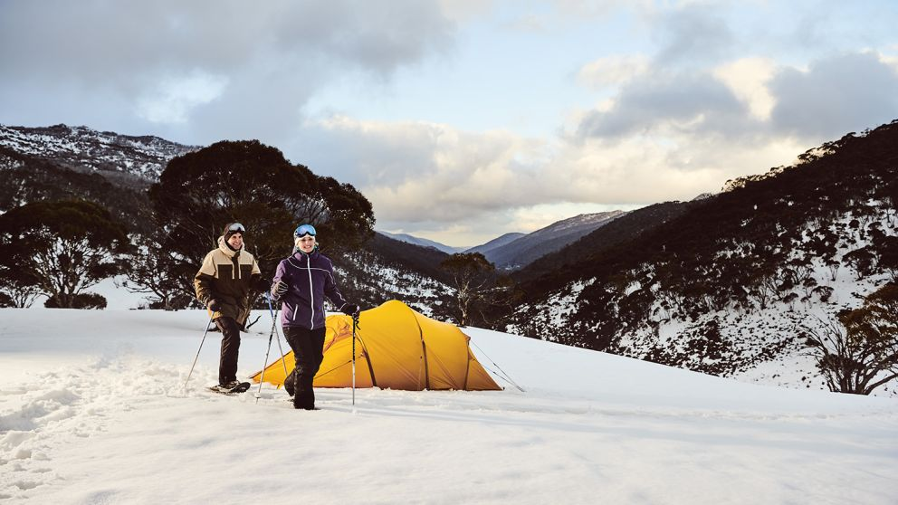 Couple snowshoeing by their campsite through Dead Horse Gap, Thredbo in the Snowy Mountains