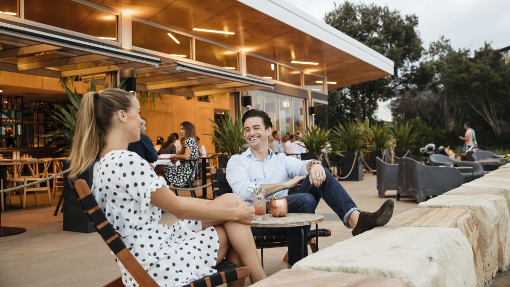 Couple enjoying evening drinks at The BOX on the Water restaurant and bar at Ettalong Beach, Central Coast