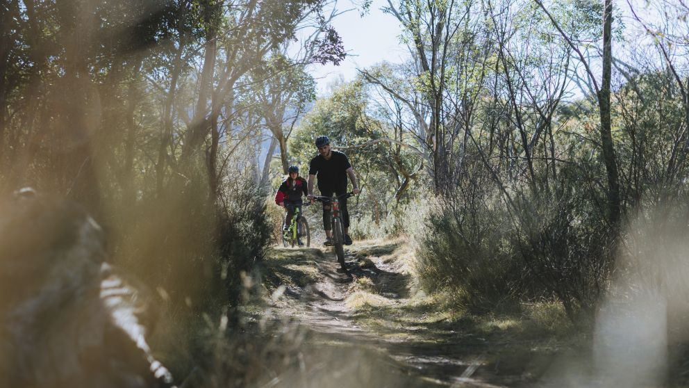 Couple enjoying a day of mountain biking on the Thredbo Valley Track in Kosciuszko National Park