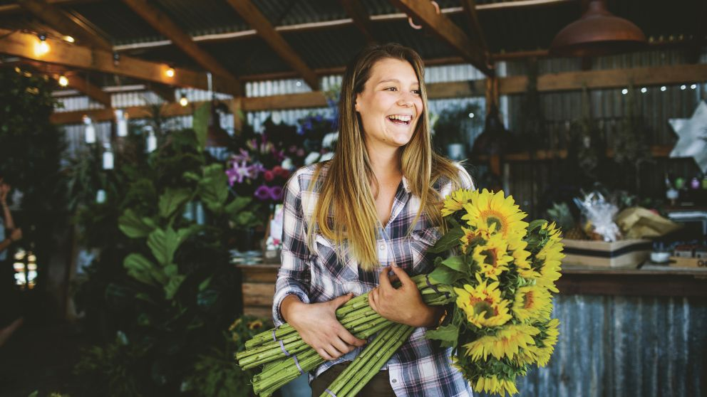 Woman with a bunch of sunflowers at The Farm, Byron Bay