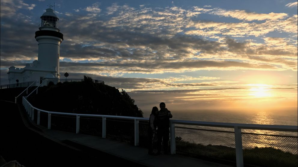 A couple enjoying a private moment watching Australia's first mainland sunrise at Cape Byron, North Coast