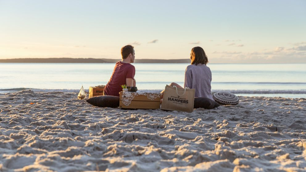 Couple enjoying a picnic packed by Hyams Beach Hampers at Blenheim Beach, Jervis Bay