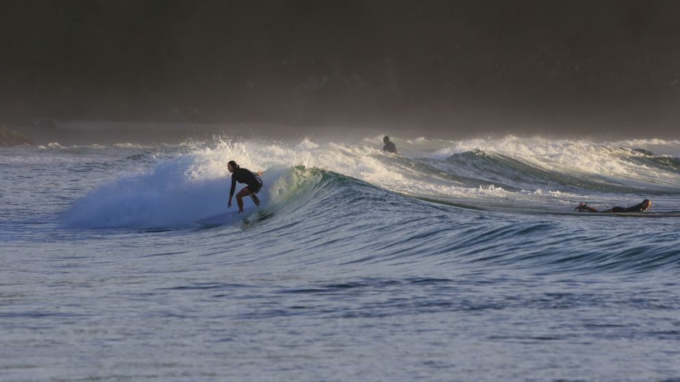 Woman enjoying a morning surf at Diggers Beach, Coffs Harbour