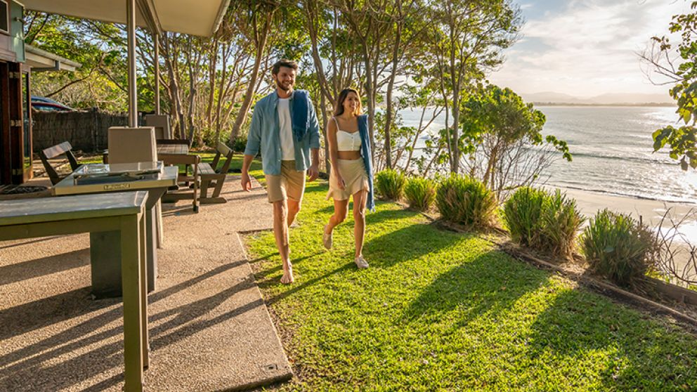 Couple walk through back garden by the beach at Mildenhall cottage in Byron Bay, North Coast