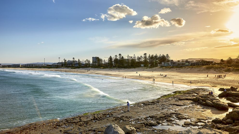 People enjoying the sand and surf at Main Beach in Wollongong, South Coast