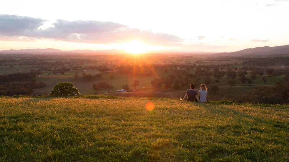 Couple enjoying a glass of wine at sunset in Tamworth's countryside