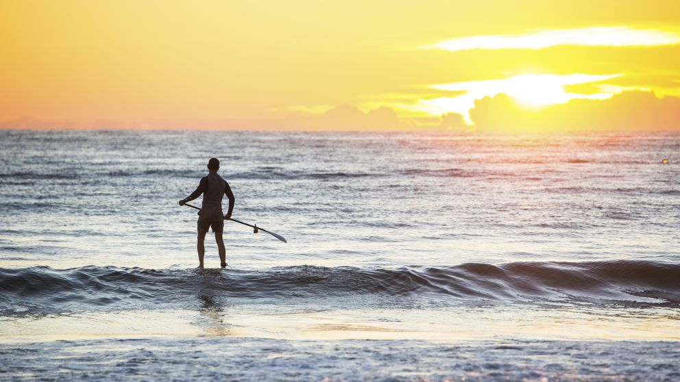 Man heading out for a morning of stand-up paddleboarding at Tathra Beach, Tathra