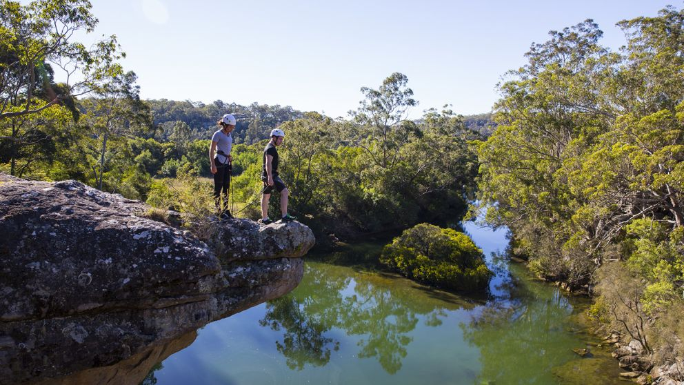 Couple ready to abseil off a clifftop in the Shoalhaven region near Nowra