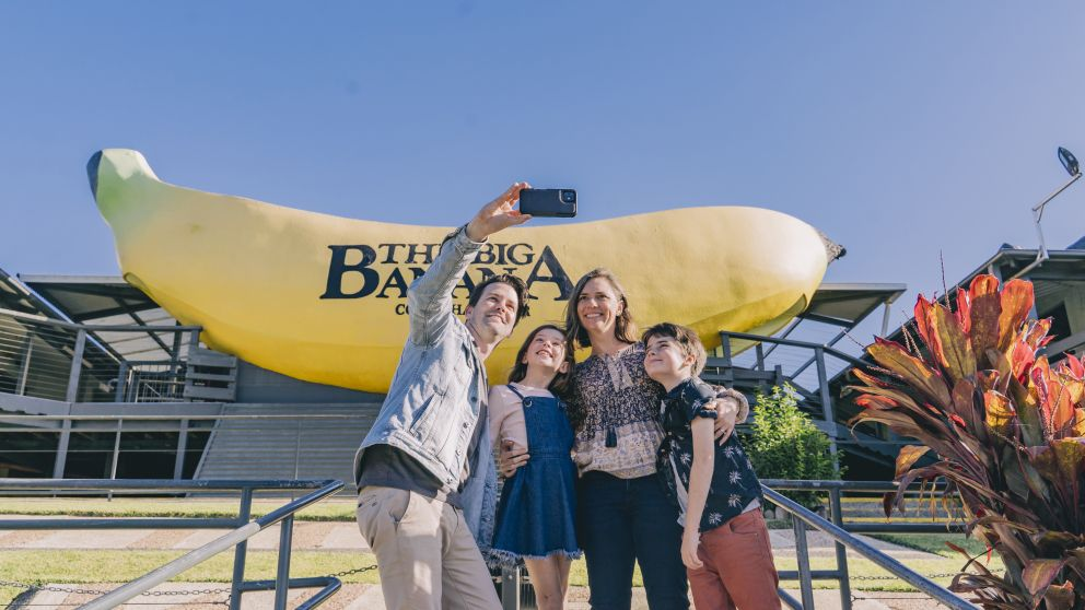 Family taking a selfie in front of The Big Banana in Coffs Harbour, North Coast
