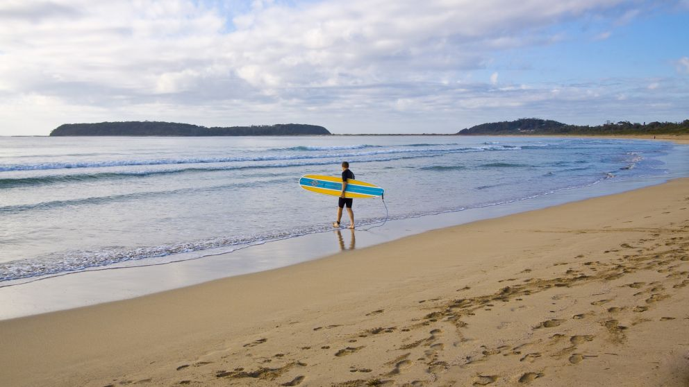 Surfer on Broulee Beach, Eurobodalla, South Coast - Credit: Jonathan Poyner - Eurobodalla Coast Tourism