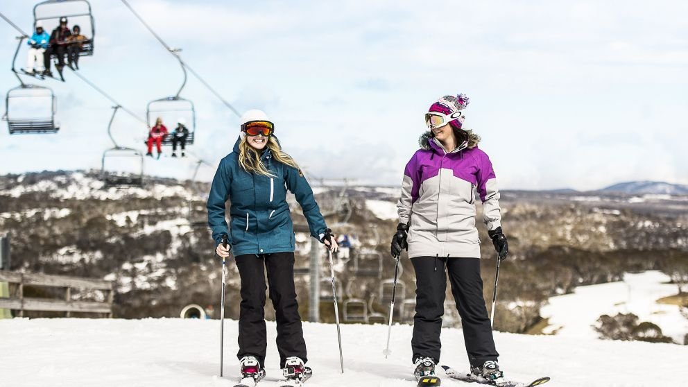 Friends skiing near ski lifts at Selwyn Snowfields in the Snowy Mountains