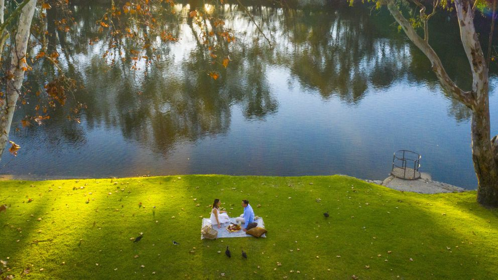 Couple enjoying a riverside picnic at Noreuil Park in Albury, The Murray