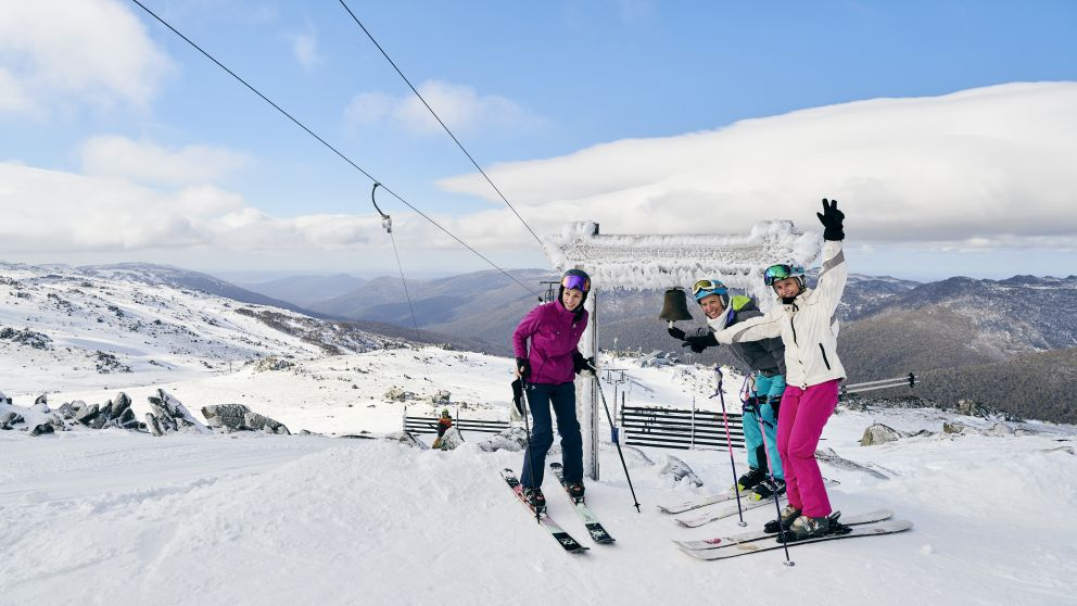 Skiers ringing the Thredbo Community Bell at Australia's Highest Lifted Point, Thredbo in the snowy Mountains