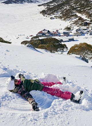 Child making snow angels at Charlotte's Pass in the Snowy Mountains