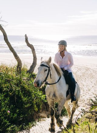 Woman enjoying a horse-riding experience with Zephryr Horses in Byron Bay