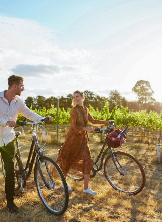 Couple enjoying a bike ride around the Clonakilla Wines vineyard in Murrumbateman, Yass Area