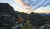 Hiker watching sunset over volcanic rock formations, Warrumbungle National Park