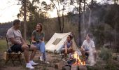 Family enjoying a campfire by their tent on the Hawkesbury River in Lower MacDonald