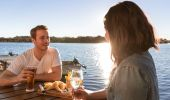Couple enjoying fish and chips by the water at Tuross Boatshed & Cafe, Tuross Head