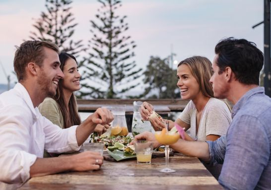 Friends enjoying food and drink at Mumbo Jumbos Beachhouse, Terrigal in Gosford, Central Coast