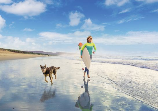 Woman and her pet dog out for a morning surf at Shoalhaven Heads, South Coast