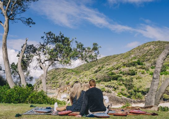 Couple enjoying a romantic picnic set up by Fuller Food Co. at Little Bay Picnic Area, South West Rocks, Macleay Valley Coast, North Coast