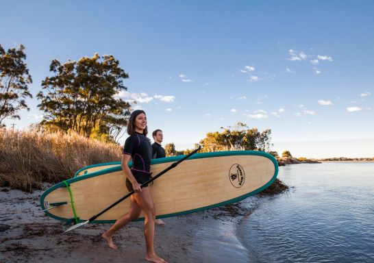 Couple enjoying a day of stand up paddleboarding on Lake Illawarra in the South Coast of NSW