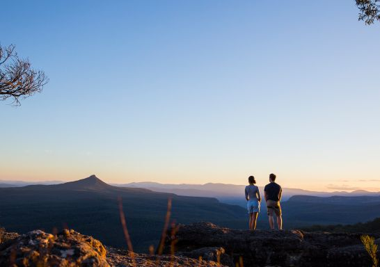 Couple enjoying panoramic views across to Pigeon House Mountain (Aboriginal: Didthul) in Morton National Park