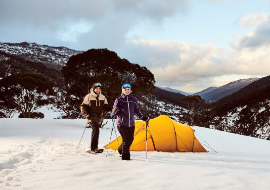 A couple snowshoeing by their campsite through Dead Horse Gap, Thredbo in the Snowy Mountains