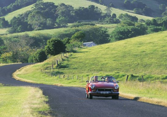 Couple driving red MG car through countryside at Gerringong in Kiama Area, South Coast