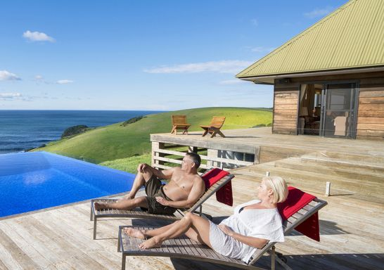 Couple relaxing by the pool at Ocean Farm luxury accommodation in Gerringong, Kiama Area, South Coast