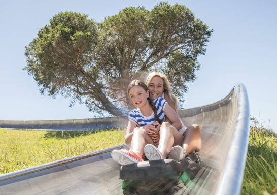 Mother and daughter enjoying water slide at Jamberoo Action Park in Jamberoo, Kiama Area, South Coast
